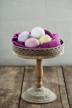 cakestand: Easter eggs on rustic wooden stand on wood