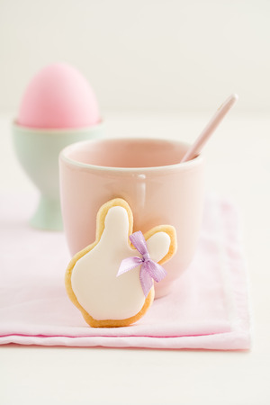 Easter bunny sugar cookie with hair ribbon, a pink cup and an Easter egg photo
