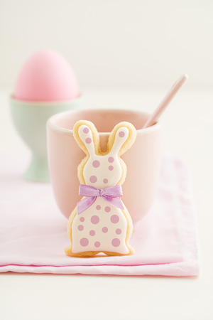 Easter bunny sugar cookie with bow tie and polka dots and a pink cup photo