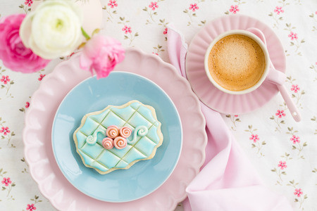 garnished: Decorated and garnished floral sugar cookie on a plate with a coffee and ranunculus flowers