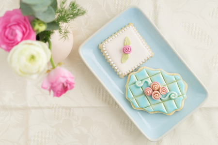 garnished: Two decorated and garnished floral sugar cookies on a plate with ranunculus flowers