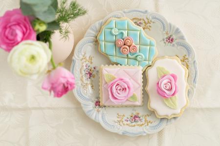 marcos decorados: Tres galletas de azúcar florales adornados y decorados en un plato con flores ranúnculo Foto de archivo