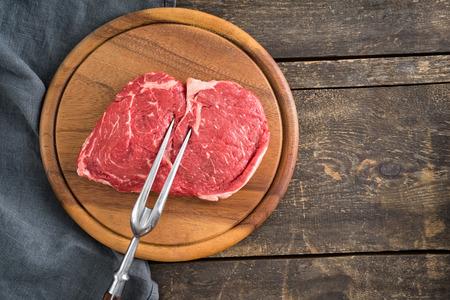 costilla: Fresh rib-eye steak crudo con gran tenedor en plato de madera y mesa de madera Foto de archivo