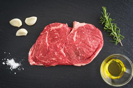 ribeye: Fresh uncooked rib-eye steak with garlic, salt, olive oil and rosemary on black background
