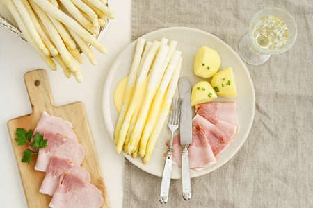 White asparagus with potatoes, boiled ham and hollandaise sauce