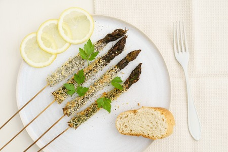 grilled vegetables: Panko fried violet asparagus skewers with baguette and lemon slices Stock Photo
