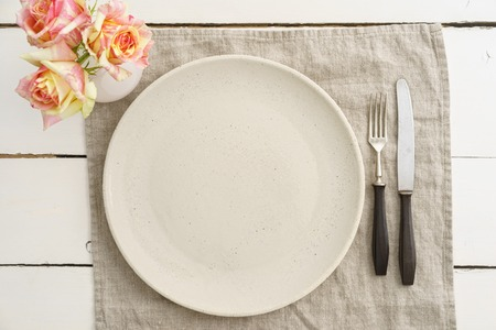 plate setting: Empty beige plate with vintage silverware on linen cloth with roses Stock Photo
