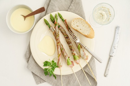 wine sauce: Grilled green asparagus skewers wrapped with bacon served with sauce hollandaise, white wine and baguette