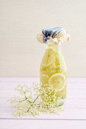 lemon slices: Elderflowers, sugar and lemon slices in a bottle for making elderflower syrup Stock Photo