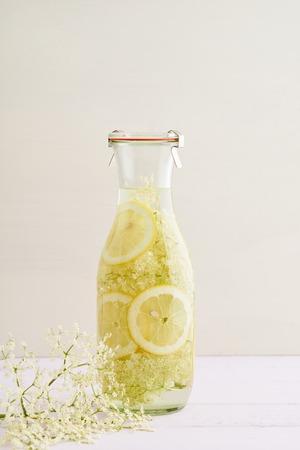 lemon slices: Elderflowers, sugar and lemon slices in a bottle for making elderflower syrup Stock Photo