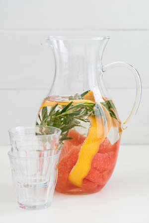 copa de agua: Infused water with pink grapefruit, orange peels and rosemary in a pitcher