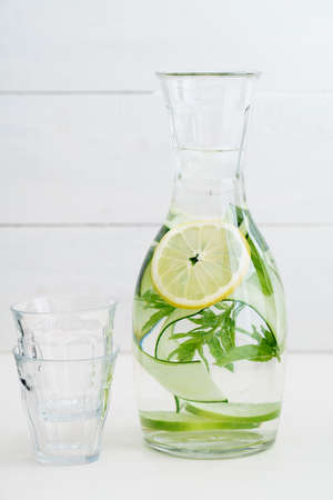 Infused water with cucumber, lemons and mint in a pitcher Stock Photo