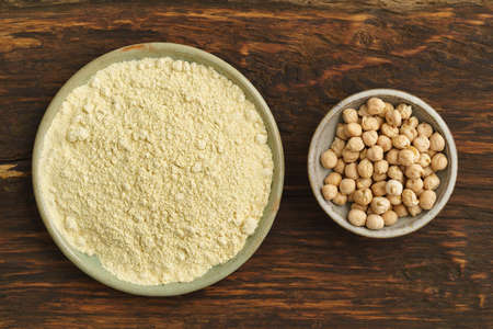 chickpea: Chickpea seeds and chickpea flour in small bowls Stock Photo
