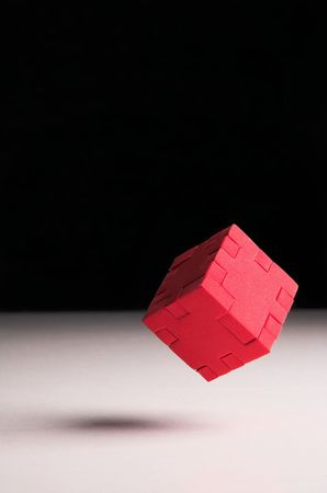 enigma: Floating red puzzle cube Stock Photo