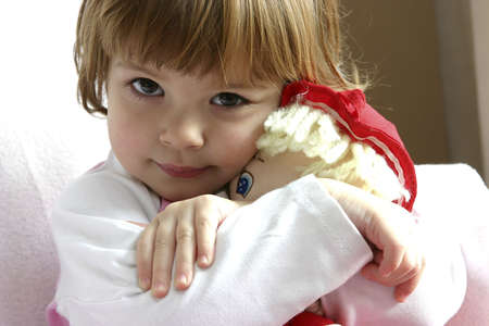 Little girl cuddling her doll with love.