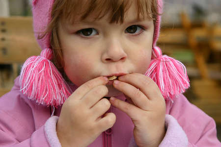 unhealthy snack: Child eating potatoe chips outdoors.