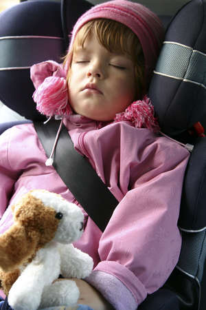 child seat: Child sleeping in a car.