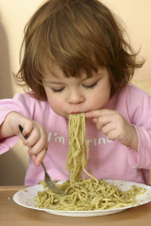 dirty girl: little child eating pasta with pesto sauce