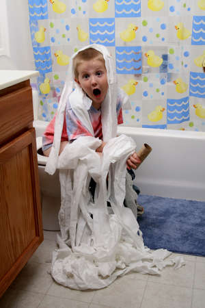 messy: boy gets crazy with the toilet paper Stock Photo