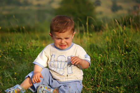 sobbing: Cute  sitting in the grass and crying. Stock Photo