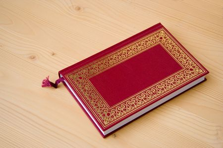 bookish: Book. Book on table. Red book. Book with red cover and arabesque decoration. Wood background.