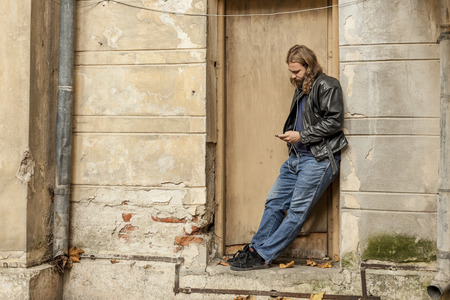 urban scene: Blond long hair and beard young adult hipster man listening music. Outdoor, urban scene.