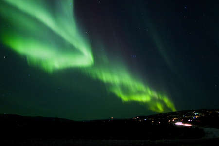 intrigue: Northern lights over hill
