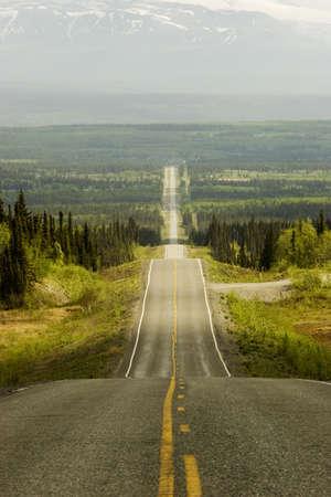 over the hill: Terreno excesivo de la colina del camino en Alaska. Edherton Hwy.