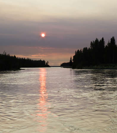 amounts: Forest fire smoke makes Sun red, and all around is different due to large amounts of smoke.. Stock Photo