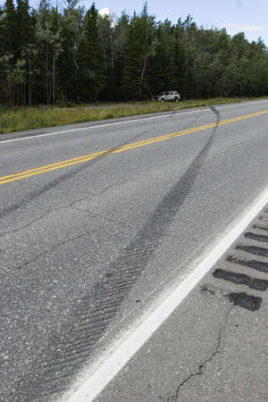 careless: Tire marks and car rolled over - proof of someones careless driving Stock Photo