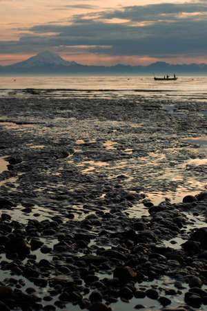 Low tide beach of Cook Inlet with fisherman boat in the background. Volcanoe visible at the very background, sunset environment photo