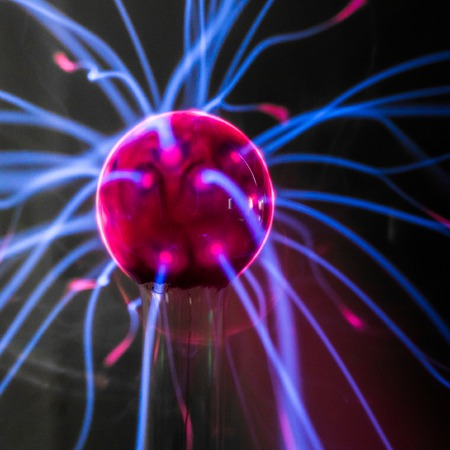 Plasma ball  with magenta-blue flames isolated on a black background. photo