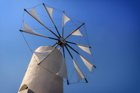 Old windmill over blue sky photo