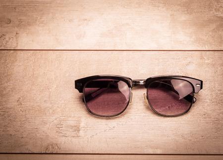 eye wear: black sunglasses on wood floor Stock Photo