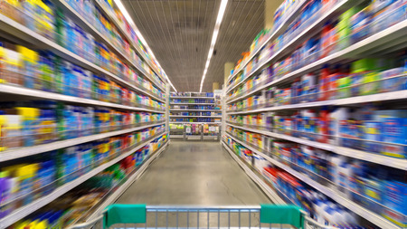 man pushing: Shopping Cart View on a Supermarket Aisle and Shelves - Image Has a Shallow Depth of Field