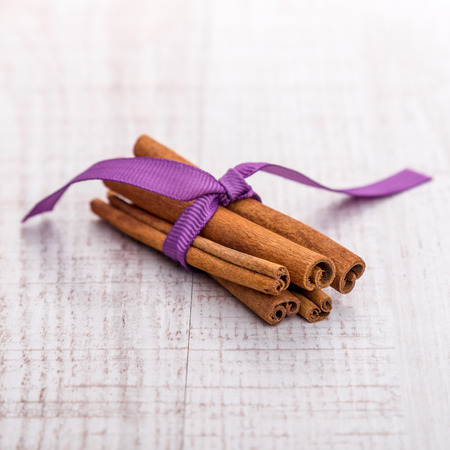 cannelle: Cinnamon isolated on wooden background. Stock Photo