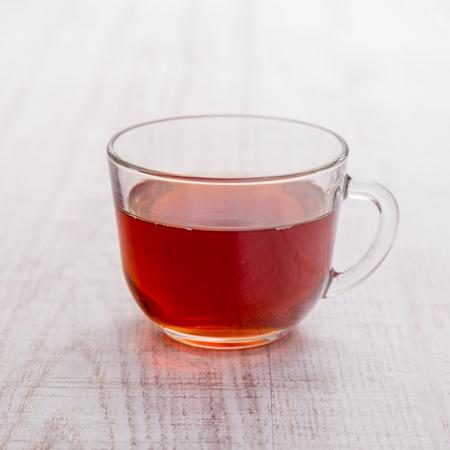 tazza di te: Tazza di tè su fondo in legno.