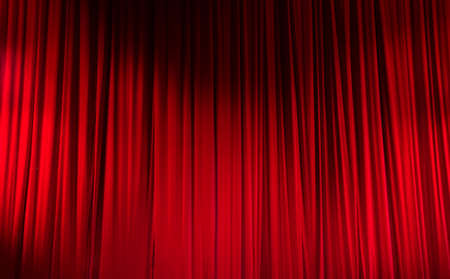 Red closed curtain with light spots in a theater. Stock Photo