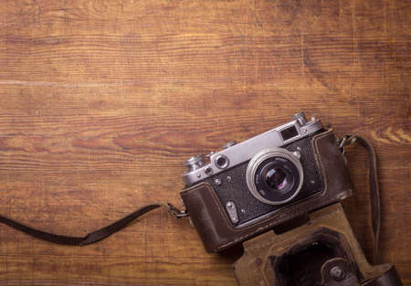 front desk: Retro camera on wood table background, vintage color tone