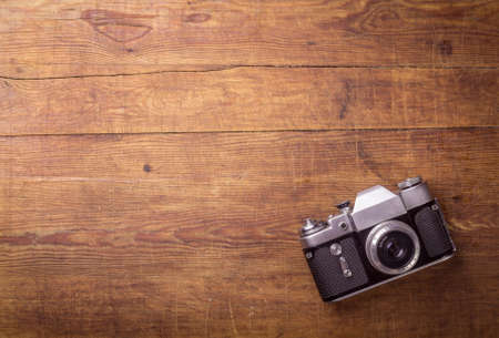 camera: Retro camera on wood table background, vintage color tone
