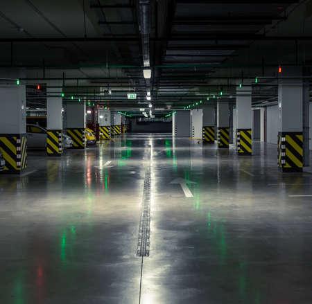 dark city: Parking garage, underground interior with a few parked cars.