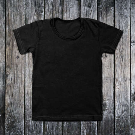 layout template: Black blank t-shirt on wooden background. Stock Photo