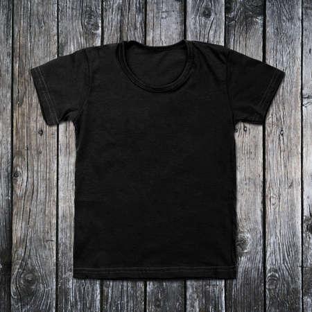 vestidos antiguos: Negro camiseta en blanco sobre fondo de madera.