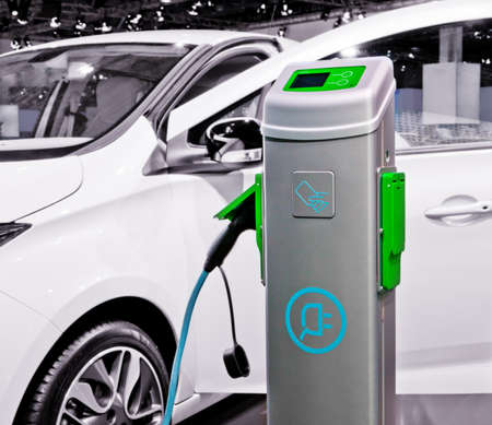 being: Plug-in electric car being charged.