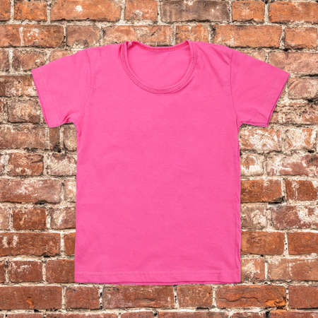 blank t shirt: Pink blank t-shirt on dark brick background. Stock Photo