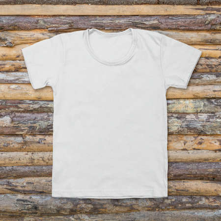 White blank t-shirt on dark wood desk. Stock Photo
