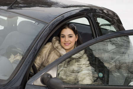 Young woman in a fur coat sitting in the car Stock Photo