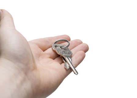 Hand holding a key isolated on a white background photo