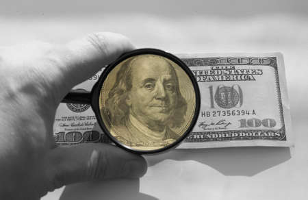 one hundred dollars and magnifying glass photo