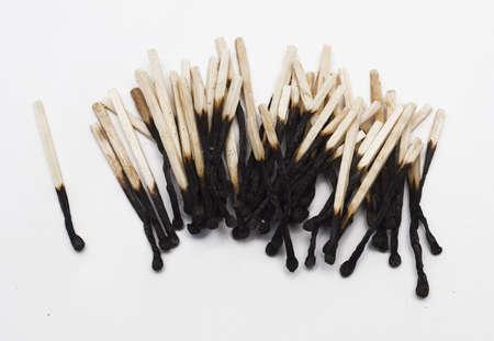 spent: burnt matchsticks over white background
